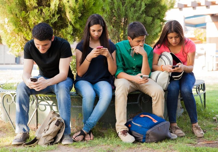 Group of teenage boys and girls ignoring each other while using their cell phones at school